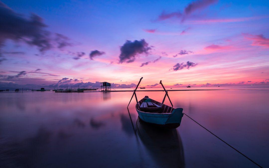 purple blue sunrise on lake with boat